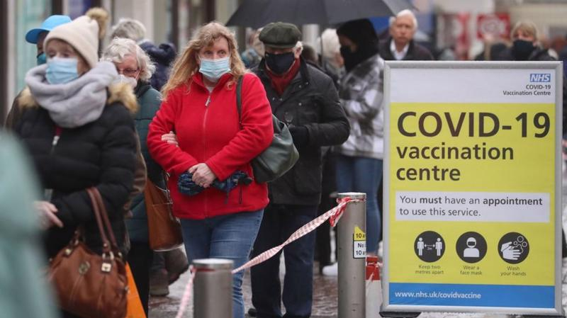 Người dân xếp hàng chờ tiêm vaccine Covid-19 tại Anh - Ảnh: AP