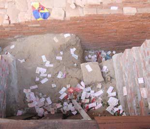 Rắc tiền công đức tại hố tháp cổ, chùa Phật Tích - Ảnh: VNN.