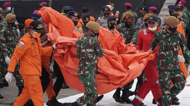 Nhân viên tìm kiếm cứu hộ mang các mảnh vỡ trục vớt từ hiện trường vụ tai nạn máy bay của hãng Sriwijaya Air - Ảnh: Bloomberg