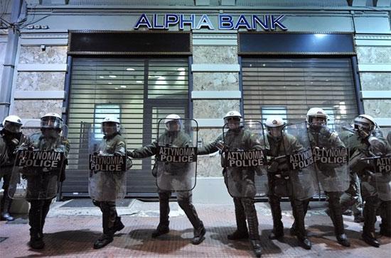 Cảnh sát chống bạo động Hy Lạp phòng ngừa những người biểu tình đang tức giận với tình trạng kinh tế của nước này. Chính phủ Hy Lạp hiện đang chạy đua với thời gian trong những nỗ lực cắt giảm thâm hụt ngân sách để chống lại những áp lực tăng lãi suất phát hành trái phiếu - Ảnh: Reuters.