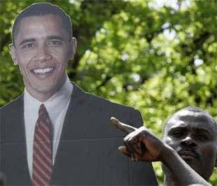 Một người đàn ông ở làng Kogelo (Kenya) - quê cha của Obama - giơ cao tấm biểu ngữ in hình vị Tổng thống mới đắc cử của nước Mỹ - Ảnh: Reuters.