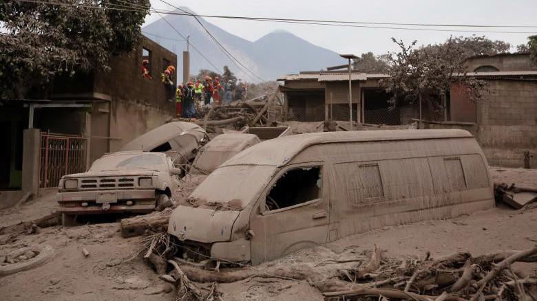 Nhà cửa và xe cộ tại một ngôi làng Guatemala bị vùi lấp trong tro bụi và nham thạch núi lửa - Ảnh: Reuters.