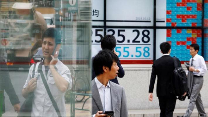 Những người bộ hành đi qua một bảng điện tử trên đường phố Tokyo hiển thị diễn biến chỉ số Nikkei của chứng khoán Nhật Bản phiên ngày 12/10 - Ảnh: Reuters.