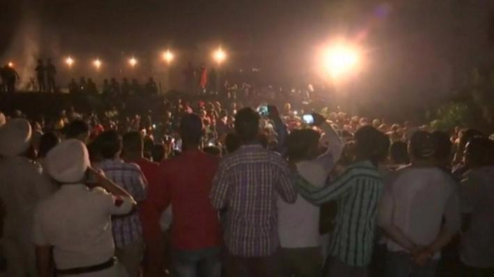 Ảnh cắt từ video cho thấy đám đông tụ tập trên đường ray để xem đốt bù nhìn trước khi đoàn tàu lao tới - Ảnh: Reuters.