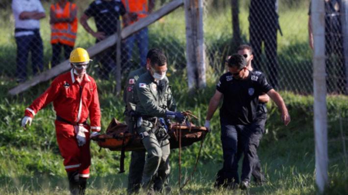 Nhân viên cứu hộ đưa một thi thể nạn nhân khỏi hiện trường vụ vỡ đập - Ảnh: Reuters.