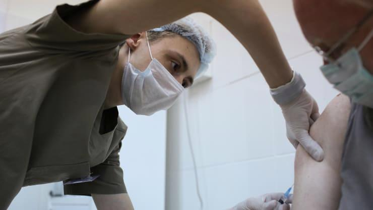 Vaccine phòng Covid-19 có tên Sputnik V đang được một nhân viên y tế tiêm cho một tình nguyện viên trong quá trình thử nghiệm - Ảnh: Bloomberg.
