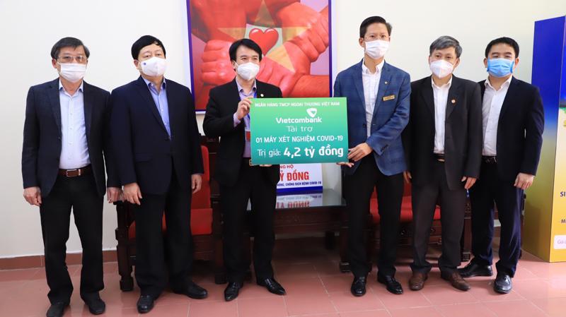 Ông Nguyễn Xuân Cao Cường - Giám đốc Vietcombank Hải Dương (thứ ba từ phải sang), thay mặt Ban lãnh đạo Vietcombank trao biển tài trợ 1 máy xét nghiệm COVID-19 cho tỉnh Hải Dương.