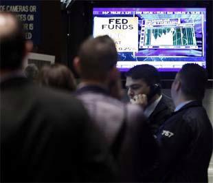 Nhà đầu tư tại Sở Giao dịch Chứng khoán New York theo dõi tuyên bố của FED trên màn hình.