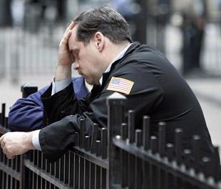 Một nhân viên môi giới bên ngoài Sở Giao dịch Chứng khoán New York. Sự thất vọng của giới đầu tư trên Phố Wall đang lan ra toàn thế giới - Ảnh: Reuters.
