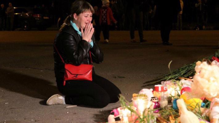 Một người phụ nữ trong lễ tưởng niệm các nạn nhân vụ xả súng trường học ở Crimea ngày 17/10 - Ảnh: Reuters.
