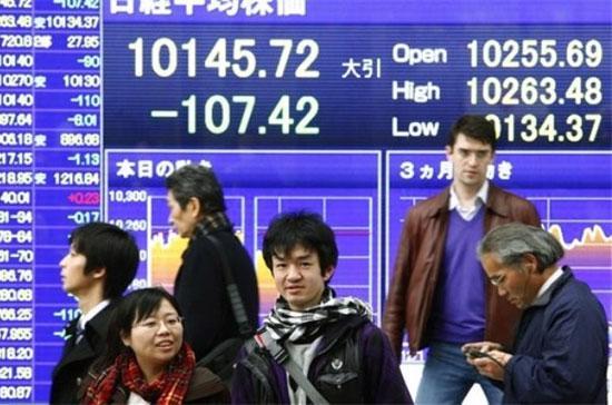Phía trước một bảng điện tử chứng khoán trên đường phố Tokyo (Nhật Bản). Tính theo tỷ lệ nợ công so với GDP, thì Nhật Bản còn nặng nợ hơn cả Mỹ - Ảnh: AP.