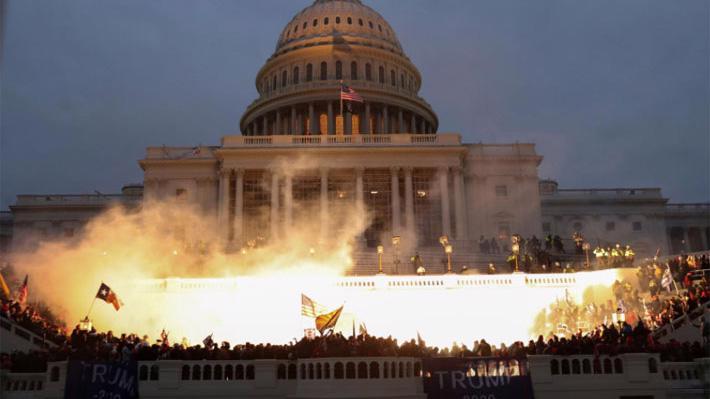 Cảnh sát dùng thiết bị nổ để giải tán đám đông người biểu tình ở tòa nhà Quốc hội Mỹ ngày 6/1 - Ảnh: Reuters.