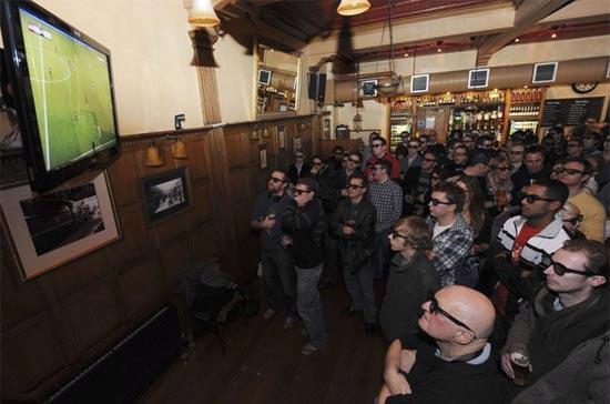 Các fan bóng đá đeo kính để theo dõi trận cầu giữa Arsenal và Manchester, được truyền hình trực tiếp bằng công nghệ 3D, tại một quán rượu ở London (Anh), ngày 31/1/2010 - Ảnh: Reuters.