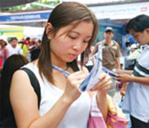Người đi tìm việc đang ghi chép thông tin về nhà tuyển dụng tại một hội chợ việc làm vừa được tổ chức ở Tp.HCM.