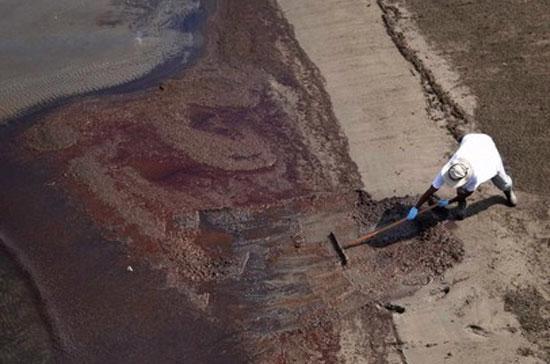 Một công nhân đang nỗ lực dọn dẹp dầu tràn bên bờ Vịnh Mexico. Cho tới thời điểm hiện nay, BP đã phải chi 1,25 tỷ USD để làm sạch dầu tràn - Ảnh: Reuters.