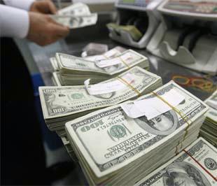 """Giới đầu tư vàng quốc tế đang đẩy mạnh bán ra vì lo ngại giá vàng có thể giảm thêm do sự mạnh lên của đồng USD. Hiện đang tồn tại một nghịch lý là kinh tế Mỹ tiếp tục lún sâu vào suy thoái, nhưng tỷ giá của đồng """"bạc xanh"""" so với các đồng tiền khác lại tăng - Ảnh: Reuters."""