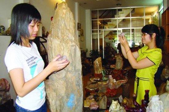 Nhân viên một cửa hàng bán các vật phẩm phong thủy và thạc anh đang chuẩn bị cho một ngày kinh doanh mới - Ảnh: U.V.