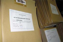 Chồng hồ sơ đăng ký nhãn hiệu trên bàn xét nghiệm viên của Cục Sở hữu trí tuệ.