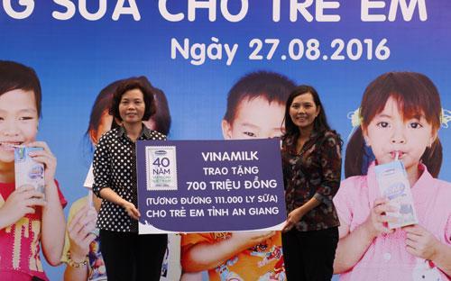 Bà Bùi Thị Hương, Giám đốc điều hành Vinamilk trao tặng bảng tượng trưng 700 triệu tương đương 111.000 ly sữa của Quỹ sữa Vươn cao Việt Nam cho trẻ em nghèo tỉnh An Giang.