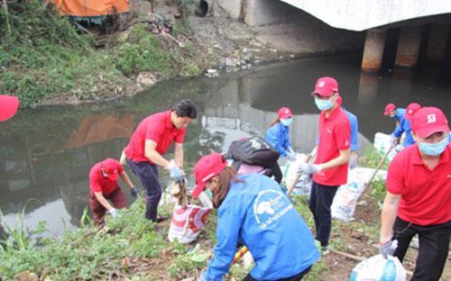 Ông Hiroyuki Saito cùng nhân viên Bridgestone Việt Namvà các tình nguyện viên làm sạch kênh rạch.