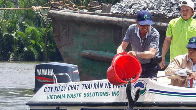 Ông David Duong và cán bộ nhân viên Công ty VWS cùng thả cá xuống kênh Rạch Chiếu, sông Cần Giuộc.