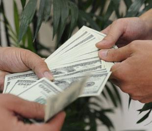 Doanh nghiệp bắt đầu đẩy mạnh bán USD cho ngân hàng sau tình trạng găm giữ kéo dài thời gian qua - Ảnh: Quang Liên.
