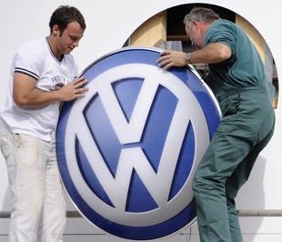 Công nhân đang lắp logo của Volkswagen vào một pa nô quảng cáo. Trong nửa đầu năm nay, thị phần toàn cầu thuộc về hãng xe lớn nhất châu Âu của Đức này đã tăng lên mức 12% từ mức 9,9% cùng kỳ năm ngoái - Ảnh: Getty.