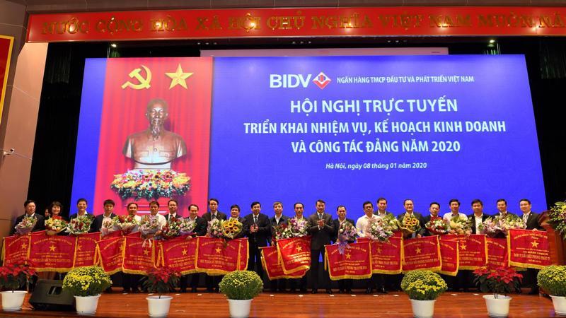 Thống đốc Lê Minh Hưng tặng cờ thi đua của Ngân hàng Nhà nước cho các tập thể, đơn vị tại BIDV. Ảnh: Thu Hương.
