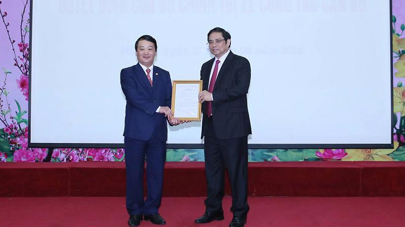 Trưởng ban Tổ chức Trung ương Phạm Minh Chính trao quyết định của Bộ Chính trị cho ông Hầu A Lềnh (trái).