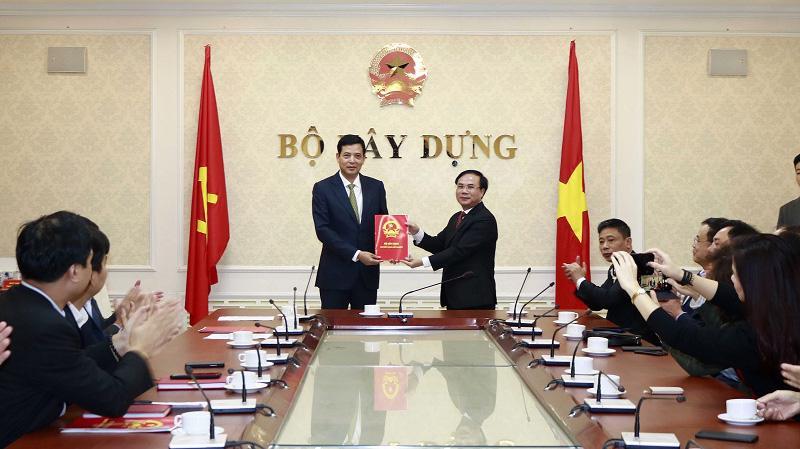Thứ trưởng Nguyễn Văn Sinh trao Quyết định của Bộ trưởng Bộ Xây dựng bổ nhiệm ông Bùi Xuân Dũng (bên trái) giữ chức vụ Cục trưởng Cục Quản lý nhà & thị trường bất động sản.