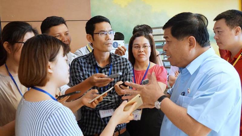 Bộ trưởng Bộ Kế hoạch và Đầu tư Nguyễn Chí Dũng trao đổi với báo chí bên hành lang Quốc hội - Ảnh: Quang Phúc