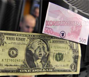 """Hai tờ tiền """"nhái"""" đồng 1 USD và 500 Euro với dụng ý châm biếm sức mạnh của USD, tại một quầy thu đổi tiền tại Frankfurt, Đức - Ảnh: Reuters."""