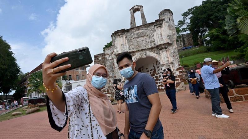 Du khách chụp ảnh tại một điểm du lịch tại Malacca, Malaysia, vào tháng 12/2020 - Ảnh: Xinhua