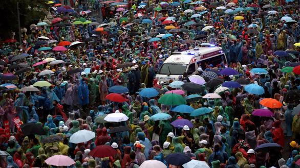 Người biểu tình đội mưa xuống đường tại tượng đài Chiến Thắng, Bangkok, Thái Lan ngày 18/10 - Ảnh: Reuters.