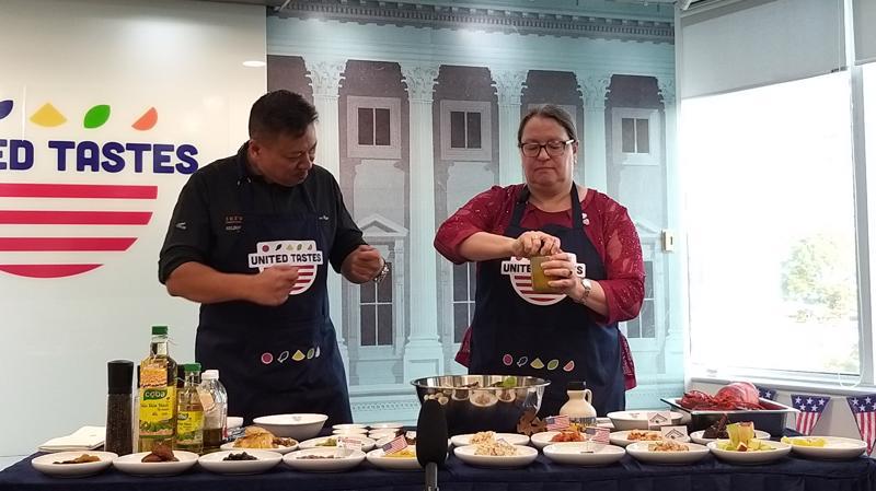 Bà Marie C.Damour, Tổng Lãnh sự Hoa Kỳ tại Tp.HCM (bên phải) cùng đầu bếp Tristan Ngo cùng thực hiện món salad.
