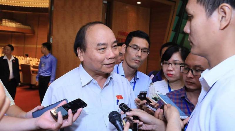Thủ tướng Nguyễn Xuân Phúc trao đổi với báo chí bên hàng lang Quốc hội - Ảnh: Quang Phúc.