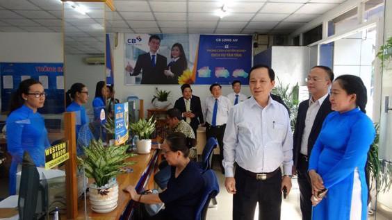 Phó Thống đốc Ngân hàng Nhà nước Đào Minh Tú (thứ 3 từ phải sang) thăm khu vực giao dịch khách hàngtrong chuyến thăm và làm việc tại CB Long An.