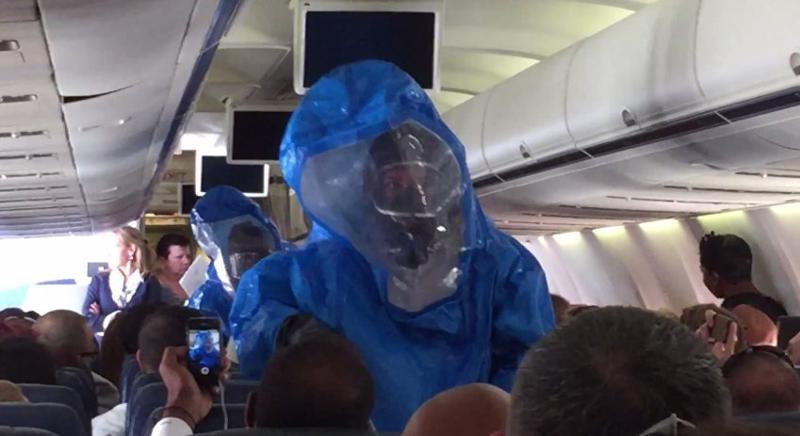 Khi máy bay hạ cánh, một nhóm nhân viên y tế trong trang phục bảo vệ từ đầu đến chân đã lên máy bay và đưa vị hành khách thích đùa này khỏi phi cơ.
