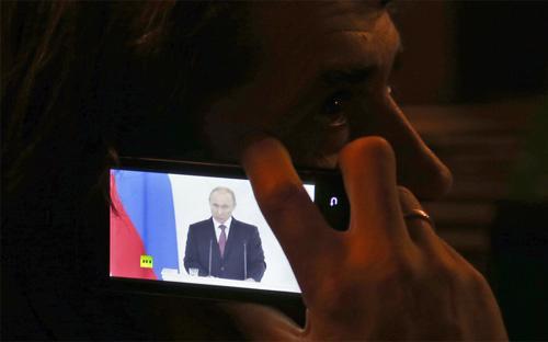 Một người dân tại Donestk, Ukraine đang lắng nghe qua điện thoại bài diễn văn về việc tiếp nhận Crimea của Tổng thống Nga Vladimir Putin, hôm 18/3 - Ảnh: AP.<br>
