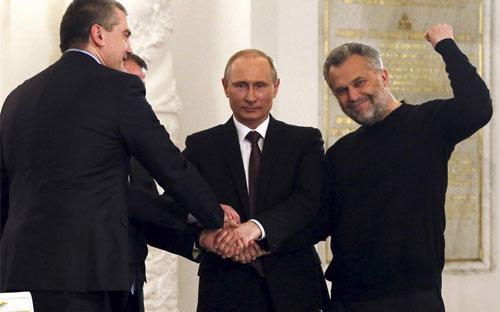 Tổng thống Vladimir Putin và các nhà lãnh đạo tại Crimea bắt tay sau lễ ký&nbsp; hiệp ước đưa Crimea trở thành một phần của Nga - Ảnh: Reuters.<br>