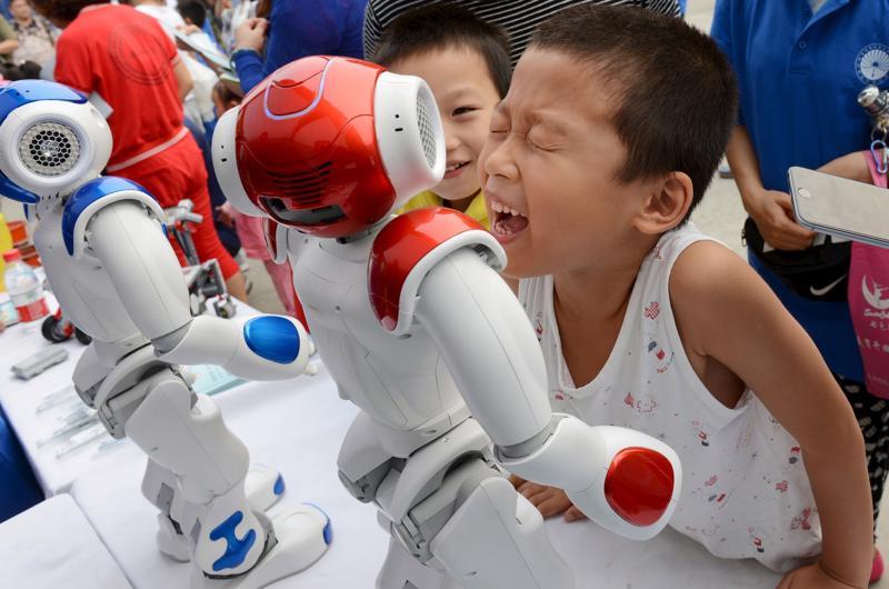 Những em bé đang nô đùa với robot trong một triển lãm ở Trung Quốc - Ảnh: Business Insider.<br>