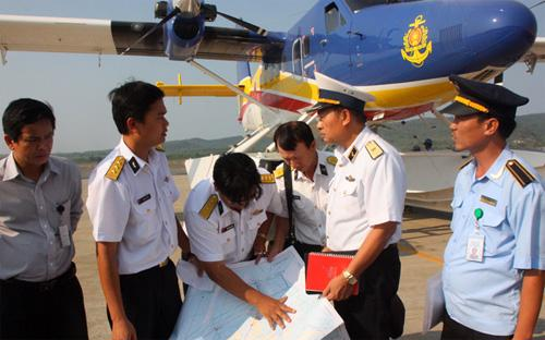 Thiếu tướng Lê Minh Thành, phó tư lệnh hải quân (thứ hai từ phải sang), hội ý với tổ bay thủy phi cơ DHC-6 tại sân bay Phú Quốc chiều 9/3, trong nỗ lực tìm kiếm máy bay mất tích của hãng Malaysia Airlines - Ảnh: Tuổi Trẻ.<br>