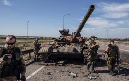 Binh sỹ nổi dậy bên một chiếc xe tăng gần như đã bị phá hủy ở Luhansk, miền Đông Ukraine - Ảnh: Reuters.<br>