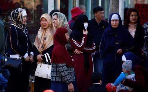 Phụ nữ người Duy Ngô Nhĩ đứng chờ xe bus ở Urumqi, thủ phủ Tân Cương, Trung Quốc - Ảnh: Reuters.