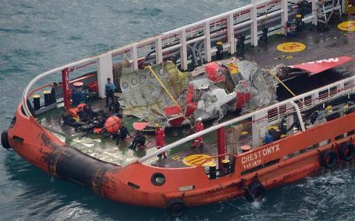 Phần đuôi máy bay AirAsia gặp nạn được trục vớt và đưa lên tàu ngày 10/1 - Ảnh: Reuters.<br>