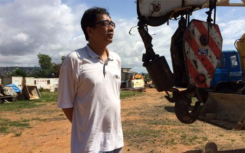 Một lãnh đạo công ty xây dựng Trung Quốc đứng trên công trường dự án đã bị đình lại vì Ebola ở Sierra Leone - Ảnh: WSJ.<br>