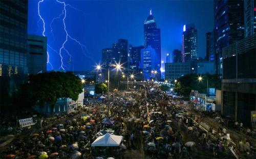 Thời tiết ở Hồng Kông hôm qua nóng nực vào ban ngày, có sớm chớp và mưa vào buổi tối, nhưng người biểu tình không hề nao núng - Ảnh: Bloomberg.<br>