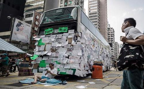 Một chiếc xe bus trên đường phố Hồng Kông ngày 30/9 dán đầy những thông điệp ủng hộ quyền dân chủ ở vùng lãnh thổ này - Ảnh: AFP.<br>