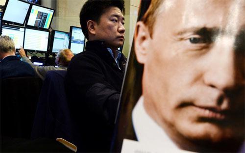 Ảnh Tổng thống Nga Vladimir Putin trên bìa một cuốn họa báo ở sàn giao dịch chứng khoán tại Moscow - Ảnh: Bloomberg.<br>