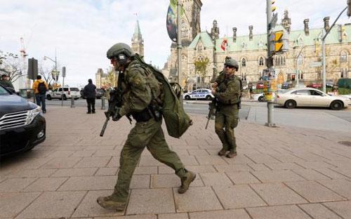 Binh sỹ thuộc lực lượng vũ trang Canada tiến vào khu vực xảy ra vụ tấn công bên ngoài tòa nhà Quốc hội ở Ottawa ngày 22/10 - Ảnh: Reuters.<br>